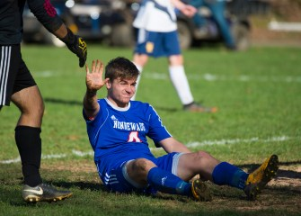 Nonnewaug's Andrew Ray raises his hand as an apology to Haddam-Killingsworth goalkeeper Trent Ferguson after slipping on the muddy field and running into him during their Class M tournament game Wednesday at Nonnewaug High School in Woodbury. Jim Shannon Republican American