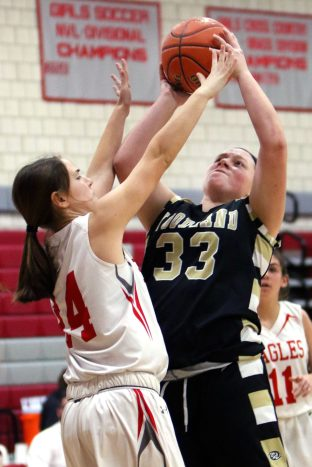 #33 Riley Kane of Woodland High goes up for a shot as #14 Morgan Matyoka of Wolcott High defends during 2nd quarter NVL basketball action in Wolcott Monday. Steven Valenti Republican-American