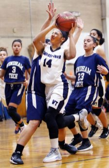 #14 Yennifer Sarmiento of Oliver Wolcott Tech. drives for a basket as #13 Brianna Macha of Windham Tech. defends during basketball action in Torrington Monday. Steven Valenti Republican-American
