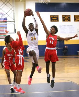 Kennedy High School's Jay Turner goes up for a shot over Derby High School's Shymar Robinson (2), Davant Addison (12), and Monte Peppers (14) during the boys varsity basketball game on Tuesday night. Emily J. Reynolds. Republican-American