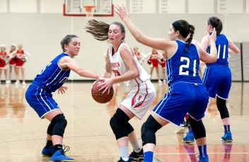 Northwestern's Jana Sanden (23) goes to the basket between Lewis Mills' Brianna Pelchar (5) and Sam Chadwick (21) during their game Tuesday at Northwestern Regional High School. Jim Shannon Republican American