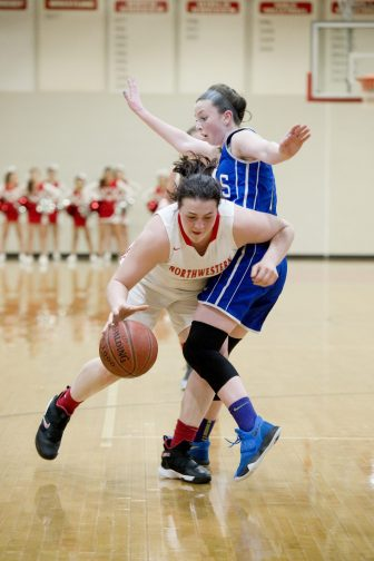 Northwestern's Natalie Lederman (22) drives to the basket while being guarded by Lewis Mills' Emily Hunt (11) during their game Tuesday at Northwestern Regional High School. Jim Shannon Republican American
