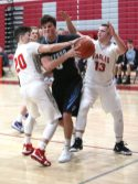 Oxford High School's Cayden Mitchell tries to keep the ball from Wolcott High School's Dane Hassan, left, and Christopher Harris during the varsity basketball game in Wolcott on Wednesday night. Emily J. Reynolds. Republican-American