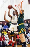 #13 Omar Rowe of Sacred Heart puts up the rebound as #30 Kyle Moser of Holy Cross defends during 1st quarter basketball action in Waterbury Thursday. Steven Valenti Republican-American