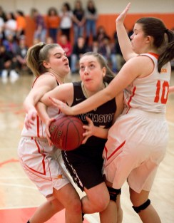 Thomaston's Emma Sanson (24) gets fouled as she drives to the basket between Terryville's Taylor Barnett (14) and Alyssa Thibodeau (10) during their Berkshire League match up Friday at Terryville High School. Jim Shannon Republican American