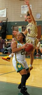 Holy Cross' Ja'Lin Waters (#25) looks to pass as Sacred Heart's Aamya Rivera (#0) defends Friday night during NVL action at Holy Cross High School. Michael Kabelka / Republican-American