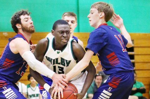 #13 Shariff Bilewu of Wilby High gets wrapped up by #13 Jarrett Michaels and #11 Tyler Lindberg of Nonnewaug High during basketball action in Waterbury Monday. Steven Valenti Republican-American
