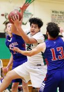#25 Anthony Abraham of Wilby high pulls down the rebound as as #13 Jarrett Michaels and #11 Tyler Lindberg of Nonnewaug High defend during basketball action in Waterbury Monday. Steven Valenti Republican-American
