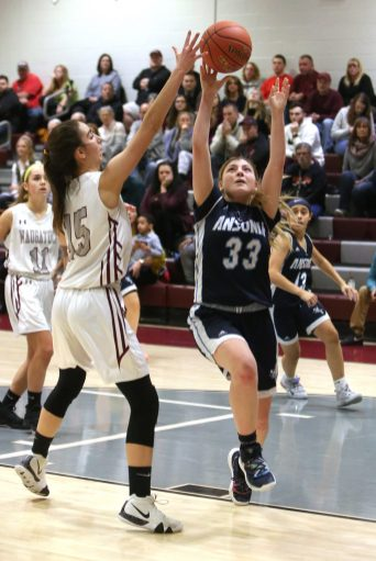 Ansonia High School's Lilly Romanowski goes up for a shot over Naugatuck High School's Sarah Macary during the girls varsity basketball game in Waterbury on Wednesday night. Emily J. Reynolds. Republican-American