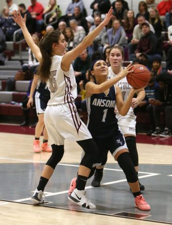 Ansonia High School's Jayda Sanchez goes up for a shot over Naugatuck High School's Sarah Macary, left, and Hailey Dehlebam during the girls varsity basketball game in Waterbury on Wednesday night. Emily J. Reynolds. Republican-American