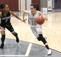 Naugatuck High School's Kaylee Jackson drives to the basket through Ansonia High School's Liz Wilson during the girls varsity basketball game in Waterbury on Wednesday night. Emily J. Reynolds. Republican-American