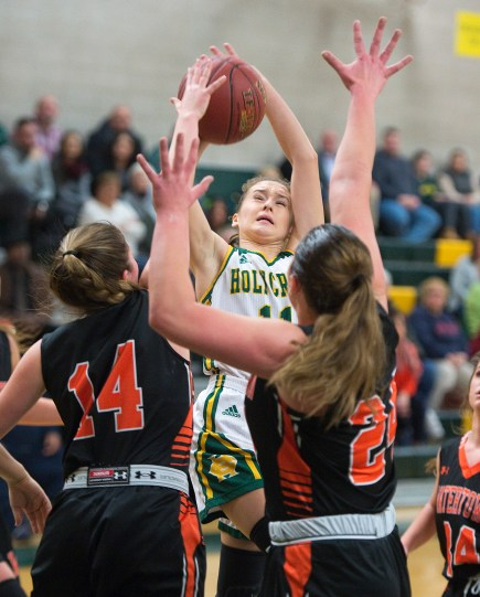 WATERBURY, CT-011819JS11- Holy Cross' Hannah Brown (11) puts up a shot over Watertown's Alyssa Santangeli (14) and Emily Deptula (24) during their game Friday at Holy Cross High School. Jim Shannon Republican American