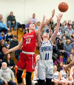 Northwestern's Jana Sanden (23) and Lewis Mills' Emily Hunt (11) battle for a rebound during their NVL match up Friday at Lewis Mills. Jim Shannon Republican American