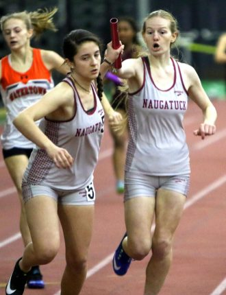 Alyssa Zarella hands off to Julia Dudek of Naugatuck during the 4x200 meter relay during the NVL indoor track championships in New Haven Monday. Steven Valenti Republican-American