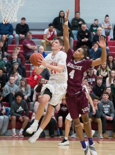 Wolcott's Brian Perzhilla (21) tries to lay up a shot in front of Naugatuck's Avery Hinnant (4) during their NVL game Tuesday at Wolcott High School. Hinnant would block the shot from behind on the play. Jim Shannon Republican American