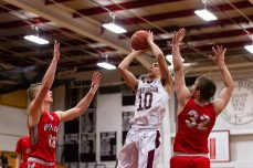 Torrington's Joel Villanueva #10 shoots a jumper in the lane against Wolcott's Jack Drewry #32 and Jeff Nicol #10 during A Boys NVL Iron Division basketball game between Wolcott and Torrington at Torrington High School in Torrington on Thursday. Torrington beat Wolcott 57-47 pulling away late in a very close game. Bill Shettle Republican-American