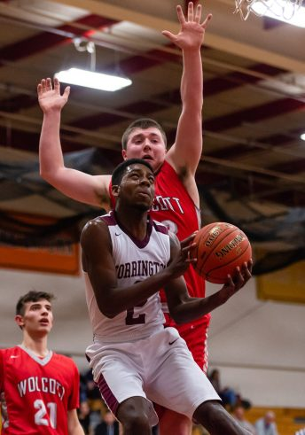 Torrington's Tyreek Davi goes up and under to the basket against the defense Wolcott's Jack Drewry #32 during A Boys NVL Iron Division basketball game between Wolcott and Torrington at Torrington High School in Torrington on Thursday. Torrington beat Wolcott 57-47 pulling away late in a very close game. Bill Shettle Republican-American