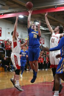 Gilbert High School's Joseph Brugmann goes up for a shot over Northwestern High School's Trent Valliere and Owen Maltby during the boys varsity basketball game at Northwestern on Friday night. Emily J. Reynolds. Republican-American