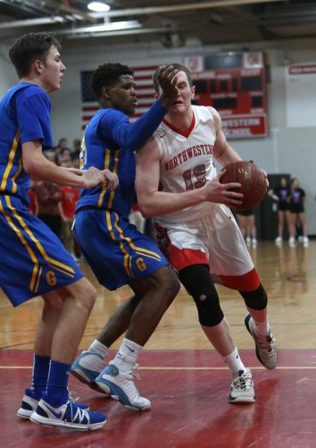 Northwestern High School's Owen Maltby drives to the basket through Gilbert High School's Dylan Crowley and Carlos Sarmiento during the boys varsity basketball game at Northwestern on Friday night. Emily J. Reynolds. Republican-American