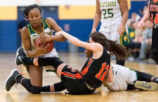Holy Cross' Cayla HOward (24) and Watertown's Nicold DeFeo (12) battle for a loose ball during their NVL semi-final game Monday at Kennedy High School in Waterbury. Jim Shannon Republican American