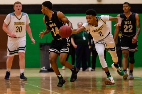 Holy Cross' Akil Evans #2 sneaks up from behind and knocks the ball away from WCA's Khali Simon #14, during the boys NVL Conference Tournament between WCA and Holy Cross at Wilby High School in Waterbury on Saturday. Bill Shettle Republican-American