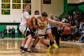 Holy Cross' Jack Greene #22 is held by WCA's Marquan Watson, going around a pick set-up by teammate Kyle Moser #30, during the boys NVL Conference Tournament between WCA and Holy Cross at Wilby High School in Waterbury on Saturday. Bill Shettle Republican-American