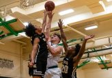 Holy Cross' Jack Greene #22 gets a shot off in between WCA defenders Jonathan Edwards #1, left, and Darrell Coombs #20, right, during the boys NVL Conference Tournament between WCA and Holy Cross at Wilby High School in Waterbury on Saturday. Bill Shettle Republican-American
