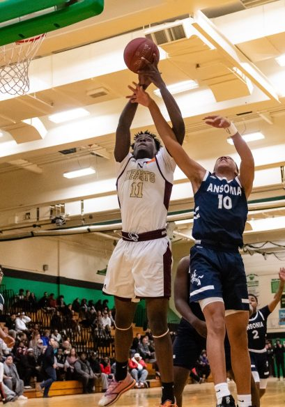 Sacred Heart's Jamaal Waters #11 goes up high grabbing a rebound away from Ansonia's Glenn Hines #10, during the boys NVL Conference Tournament between Ansonia and Sacred Heart at Wilby High School in Waterbury on Saturday. Bill Shettle Republican-American