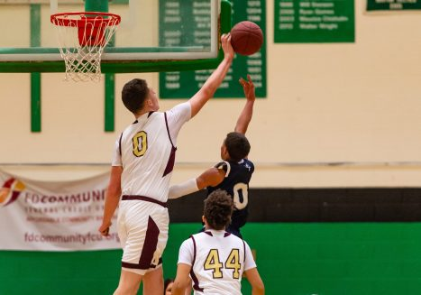 Sacred Heart's Connor Tierney #0 blocks the shot of Ansonia's Alfonso Smith #0, during the boys NVL Conference Tournament between Ansonia and Sacred Heart at Wilby High School in Waterbury on Saturday. Bill Shettle Republican-American