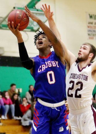 #0 Kerwin Prince of Crosby High drives to the hoop as #22 Kevin Dixon of Torrington High defends during NVL semi final basketball action in Waterbury Monday. Steven Valenti Republican-American