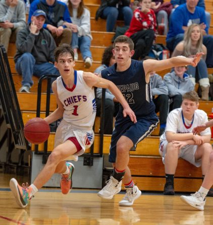 Nonnewaug's Colby Steinfield (1) looks to pass while driving the baseline past Shepaug's Jack Schneider (12) during their Berkshire League tournament game Tuesday at Lewis Mills High School in Burlington. Jim Shannon Republican American