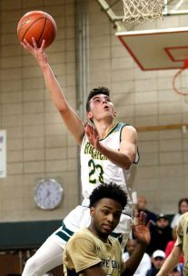 #23 Kyle Lombardi of Holy Cross goes up for a shot over #3 Jonathan Despeignes of Notre Dame-Fairfield during CIAC Division 1 first round basketball action in Waterbury Monday. Steven Valenti Republican-American