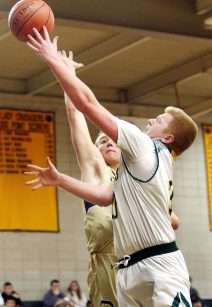 #30 Kyle Moser of Holy Cross goes up for a shot as #23 Max Mitchell of Notre Dame-Fairfield defends during CIAC Division 1 first round basketball action in Waterbury Monday. Steven Valenti Republican-American