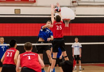 Lewis Mills' Josh Schibi #27 spikes the ball through the block of Cheshire's Nick Jennings #25, during a boys volleyball match between Lewis Mills and Cheshire at Cheshire High School in Cheshire on Friday. Bill Shettle Republican-American