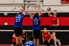 Cheshire's Aiden Godfrey #1 goes up to spike the ball against Lewis Mill players Josh Schibi #27, left, and Sam Di Sorbo #12, during a boys volleyball match between Lewis Mills and Cheshire at Cheshire High School in Cheshire on Friday. Bill Shettle Republican-American