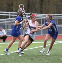 Pomperaug High School's Mia Sullivan battles two defenders on her way up the field during the girls varsity lacrosse game against Fairfield Ludlowe in Southbury on Saturday afternoon. Emily J. Reynolds. Republican-American