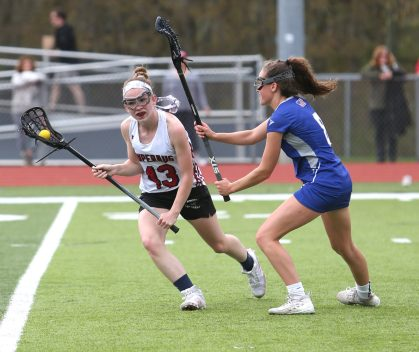 Pomperaug High School's Avery Lenczewski battles a defender on her way up the field during the girls varsity lacrosse game against Fairfield Ludlowe in Southbury on Saturday afternoon. Emily J. Reynolds. Republican-American
