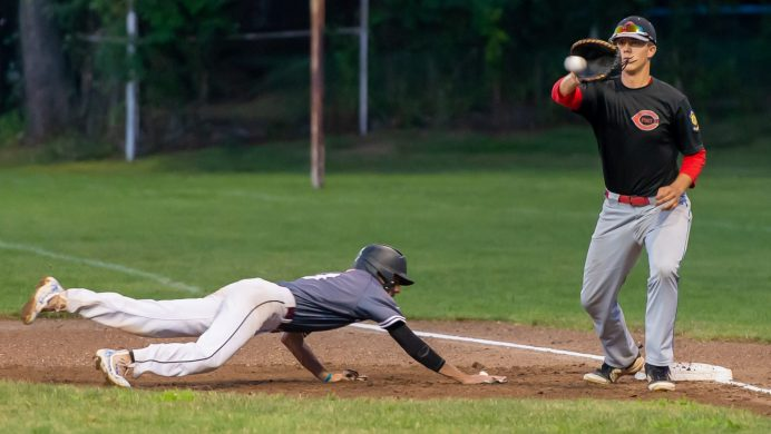Naugatuck's Zach Graveline (3) dives back safely to first base on pick off attempt while Cheshire's Benjamin Shadeck (23) covers the play during their American Legion baseball tournament game against Monday at Ceppa Field in Meriden. Jim Shannon Republican-American