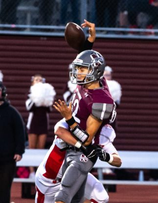 Naugatuck's Jay Mezzo (12) gets his by a Wolcott defender just as he throws a pass during their season opening game Friday at Naugatuck High School. The throw was incomplete on the play. Jim Shannon Republican-American
