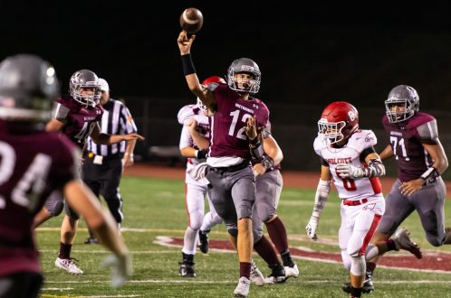 Naugatuck's Jay Mezzo (12) throws for a first down during their season opening game against Wolcott Friday at Naugatuck High School. Jim Shannon Republican-American
