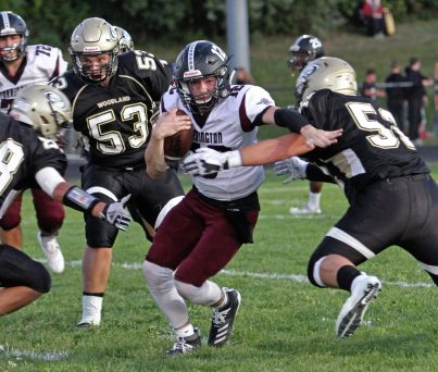 Torrington's Conrad Avallone (12) evades a tackle from Woodland's Justin Petta (52) during NVL football action at Woodland High School Friday night. Michael Kabelka / Republican-American