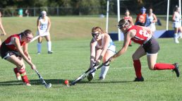 Lewis Mills High School's Morgan O'Regan battles Wamogo High School players for the ball during the girls varsity field hockey game at Lewis Mills on Wednesday afternoon. Emily J. Tilley. Republican-American