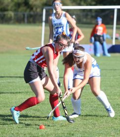 Lewis Mills High School's Hope Guillemette battles Wamogo High School's Julia Churyk for the ball during the girls varsity field hockey game at Lewis Mills on Wednesday afternoon. Emily J. Tilley. Republican-American