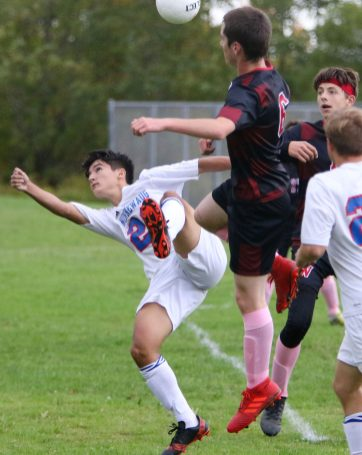 #23 Pedro Prates of Nonnewaug High back kicks a ball toward the goal past #6 Chris Orsini of Wamogo High during soccer action in Litchfield Monday. Steven Valenti Republican-American