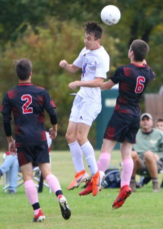 #4 Zach Thompson of Nonnewaug High heads ball past #6 Chris Orsini of Wamogo High during soccer action in Litchfield Monday. #2 Colin Ferrer of Wamogo High, at left. Steven Valenti Republican-American