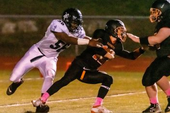 Ansonia's Cyril Jack #56, left, grabs Watertown quarterback Xavier Powell (12) for a sack deep in the Watertown end of the field, during a NVL game of the unbeatens between Ansonia and Watertown at Watertown High School on Friday. Bill Shettle Republican-American