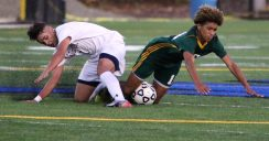 #7 Lucas Silva of Naugatuck High and #11 Kadin Talha of Holy Cross High go down while trying to control the ball during NVL Soccer action in Waterbury Monday. Steven Valenti Republican-American