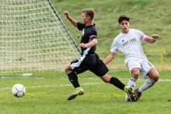 Holy Cross' Luke Zipoli (18), right, trips up Woodland's Cole Barrows (8) in the bo, resulting in a penalty kick, during a Boys NVL soccer match between Holy Cross and Woodland Regional at Woodland Regional High School in Beacon Falls on Friday. Bill Shettle Republican-American