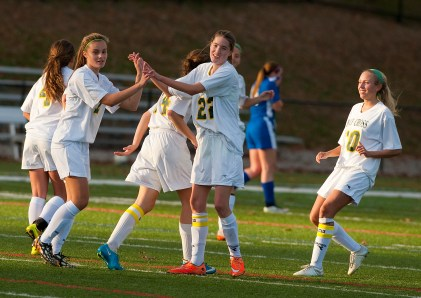 Holy Cross' Madison Bushka (7) celebrates with tam mates Jordan Gilmore (22) and Sarah Innes (10) after scoring a going during their first round game against Litchfield in the Class S girls soccer tournament Monday at Post University in Waterbury. Jim Shannon Republican-American