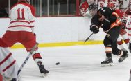#15 Sean Dunfee of Watertown-Pomperaug send a puck down ice as #11 Hunter Olson of Cheshire High defends during hockey action in Middletown Saturday. Steven Valenti Republican-American